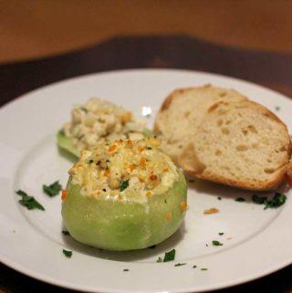 Ein Teller mit einem gefüllten Kohlrabi - im Hintergrund liegen zwei Brotscheiben