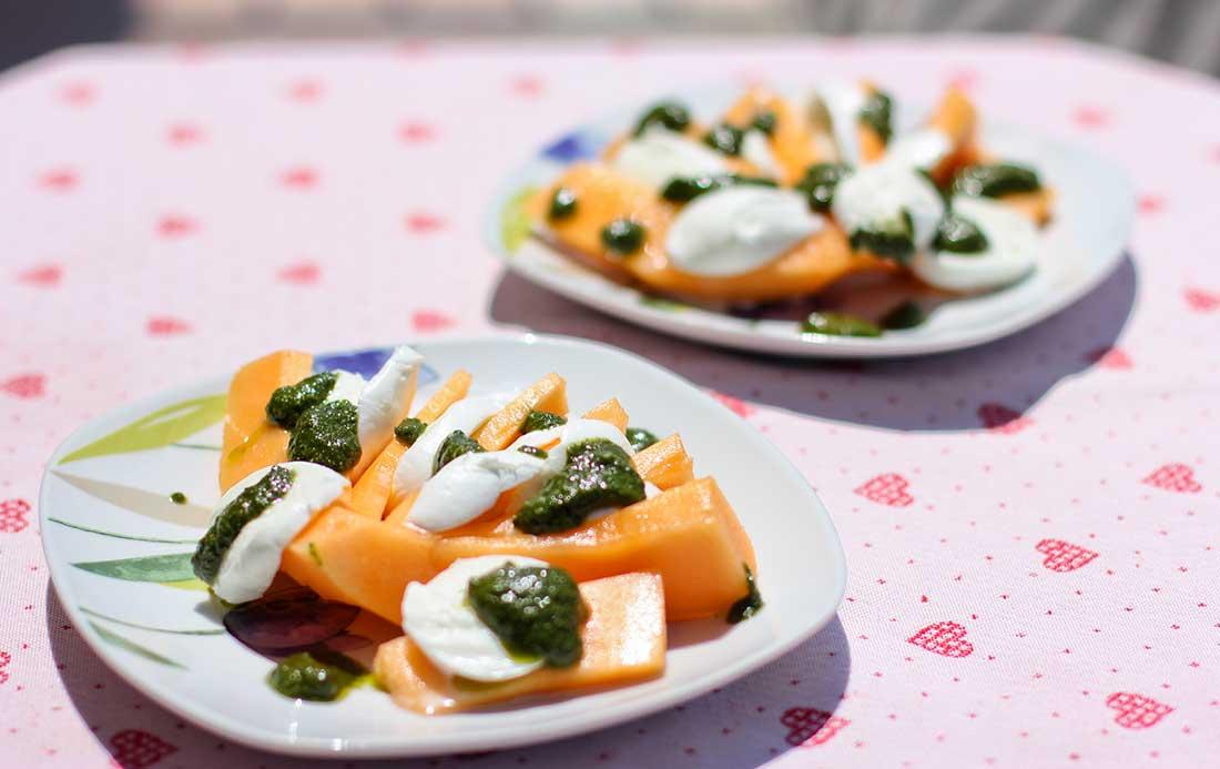 Aufgeschnittene Melone mit Mozzarella und Pesto auf zwei Tellern