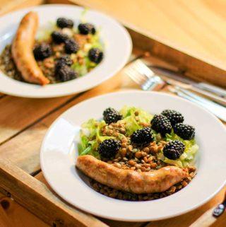 Zwei Teller, auf denen Linsen, Brombeeren, Salat und eine Salsiccia liegen. Die Teller stehen auf einem Holzbrett.