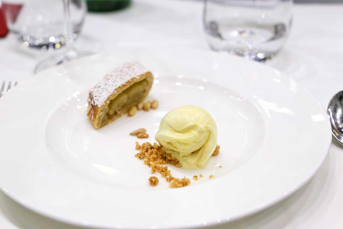 Ein Stück Apfelstrudel und eine Kugel Vanilleeis auf einem Teller