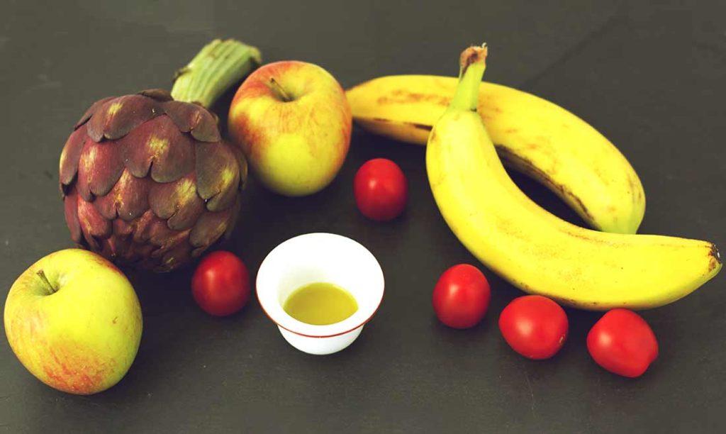 Äpfel, Tomaten, zwei Bananen, eine Artischocke und Becher Olivenöl