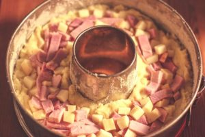 Kartoffelteig in einer runden Backform, der mit Schinken- und Käsewürfeln bestreut ist.