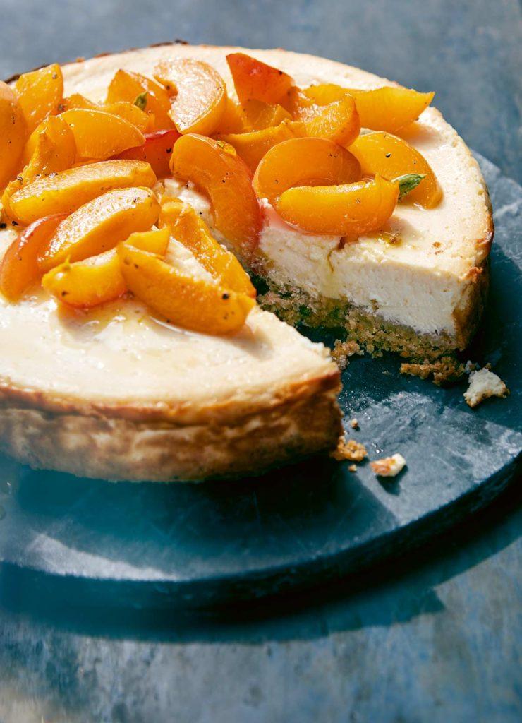 Ein angeschnittener Cheesecake mit Aprikosenbelag