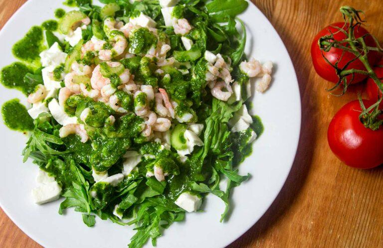 Ein Salat mit Rucola, Garnelen und Mozzarella, daneben liegen zwei Tomaten