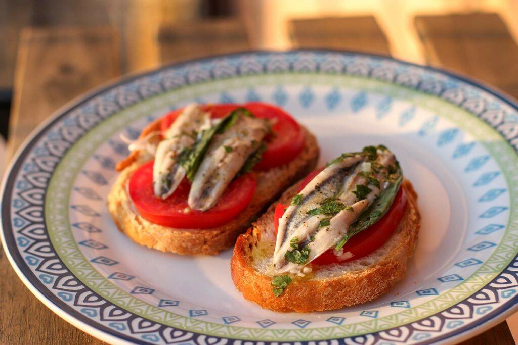 Zwei Crostini mit Tomate und Sardellen auf einem Teller