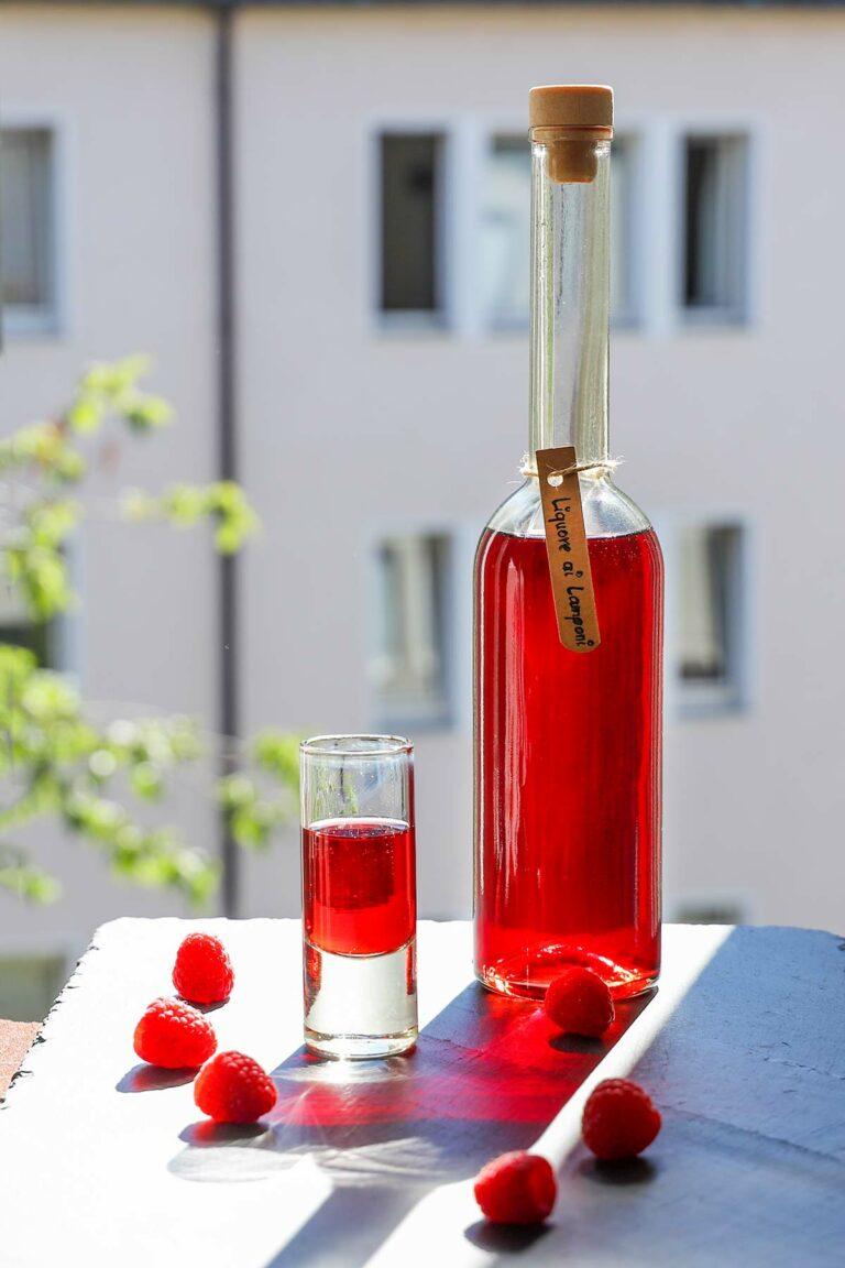 Ein Glas Himbeerlikör mit der Flasche im Hintergrund.