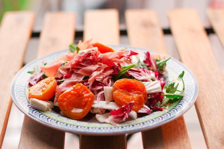 Ein Teller mit Salat, garniert mit Aprikosen und Schinken