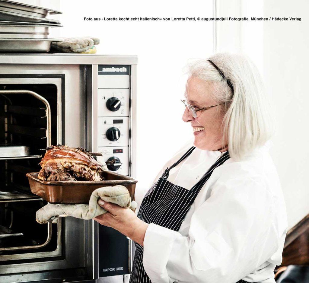Köchin Loretta Petti hält eine Ofenform mit Porchetta in der Hand