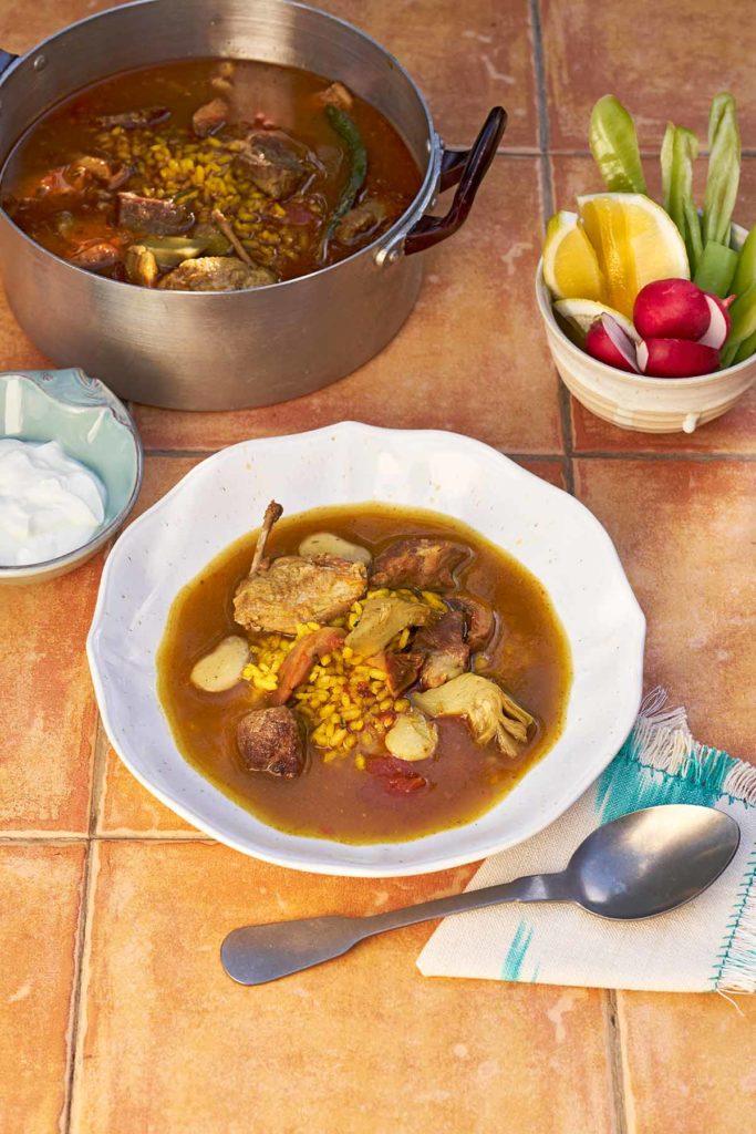 Ein Teller und Topf mit Arros Brut, dem mallorquinischen schmutzigem Reis.