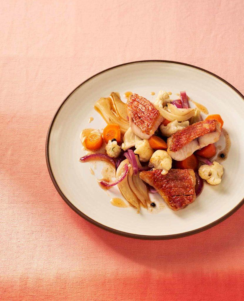 Ein Teller mit drei Rotbarbenfilets und Gemüse in Escabeche-Sauce