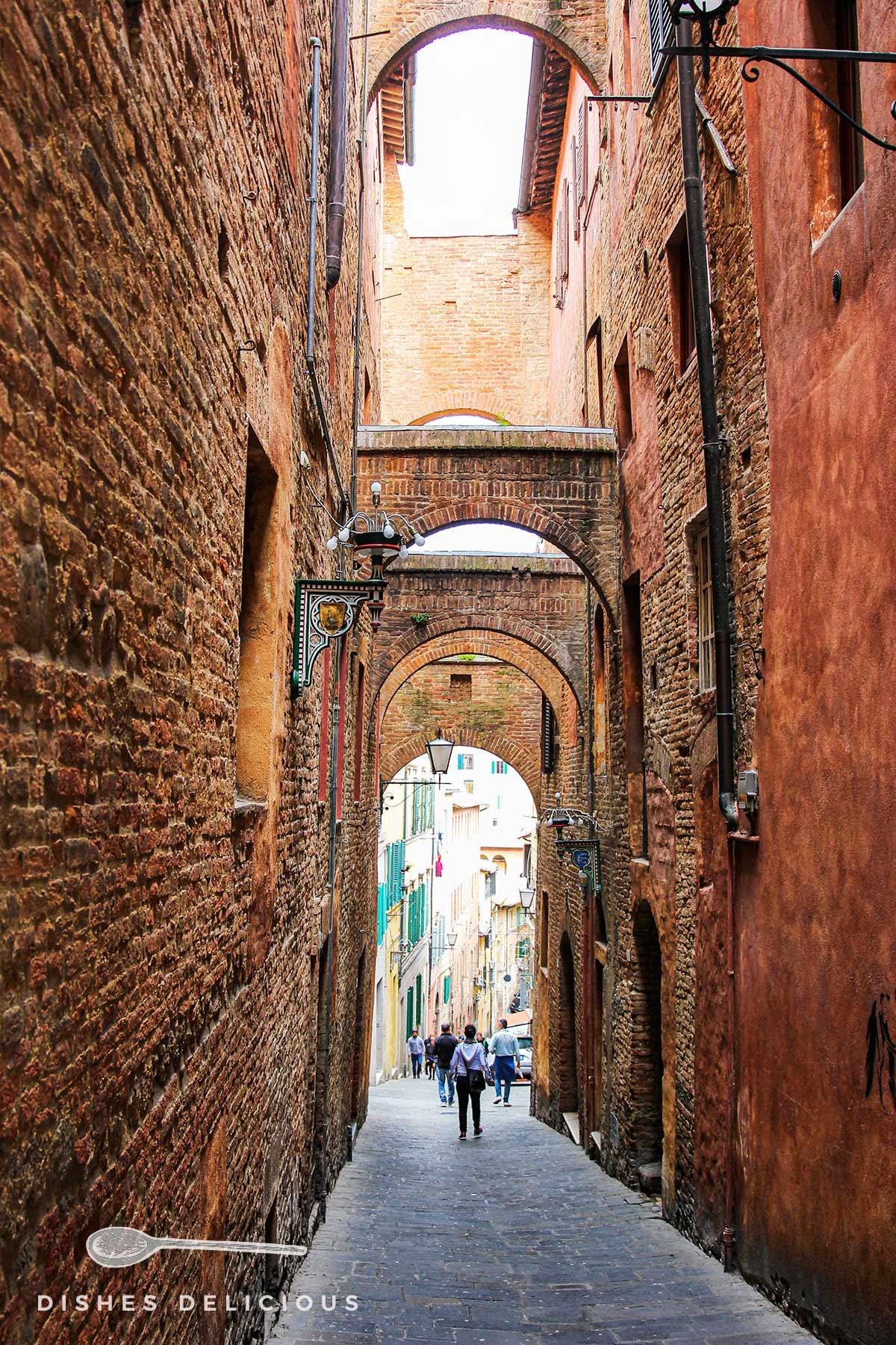 Enge Gasse mit mittelalterlichen Bögen in Siena.