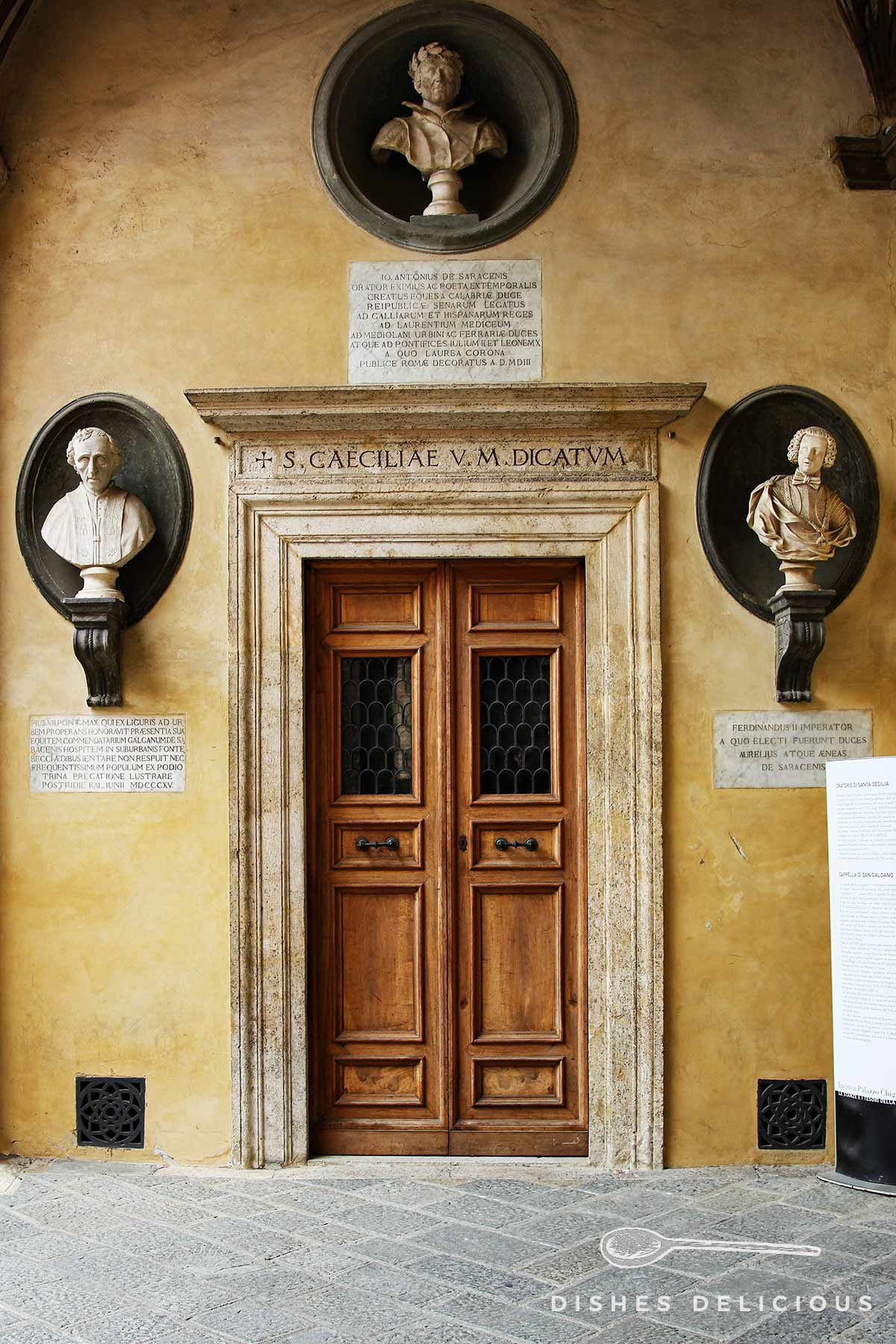 Eine alte Holztür und Steinbüsten an der Hauswand