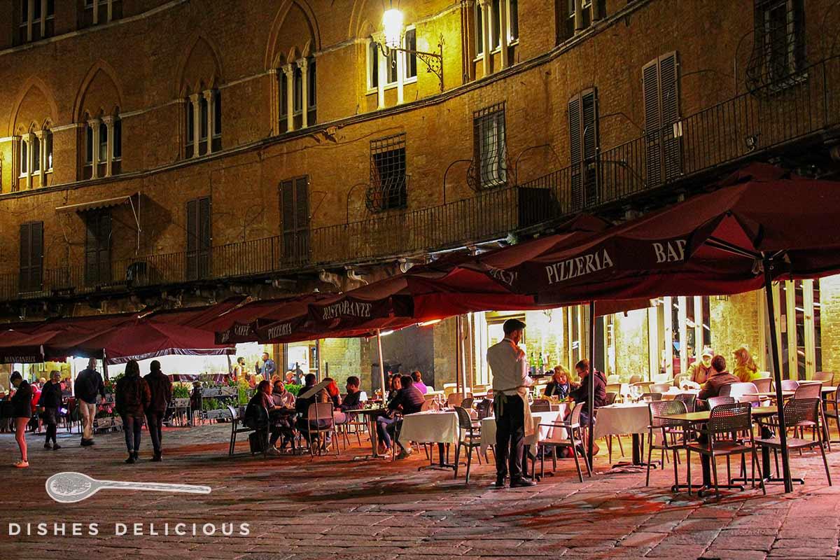 Restaurantbesucher am Abend an der Piazza del Campo in Siena