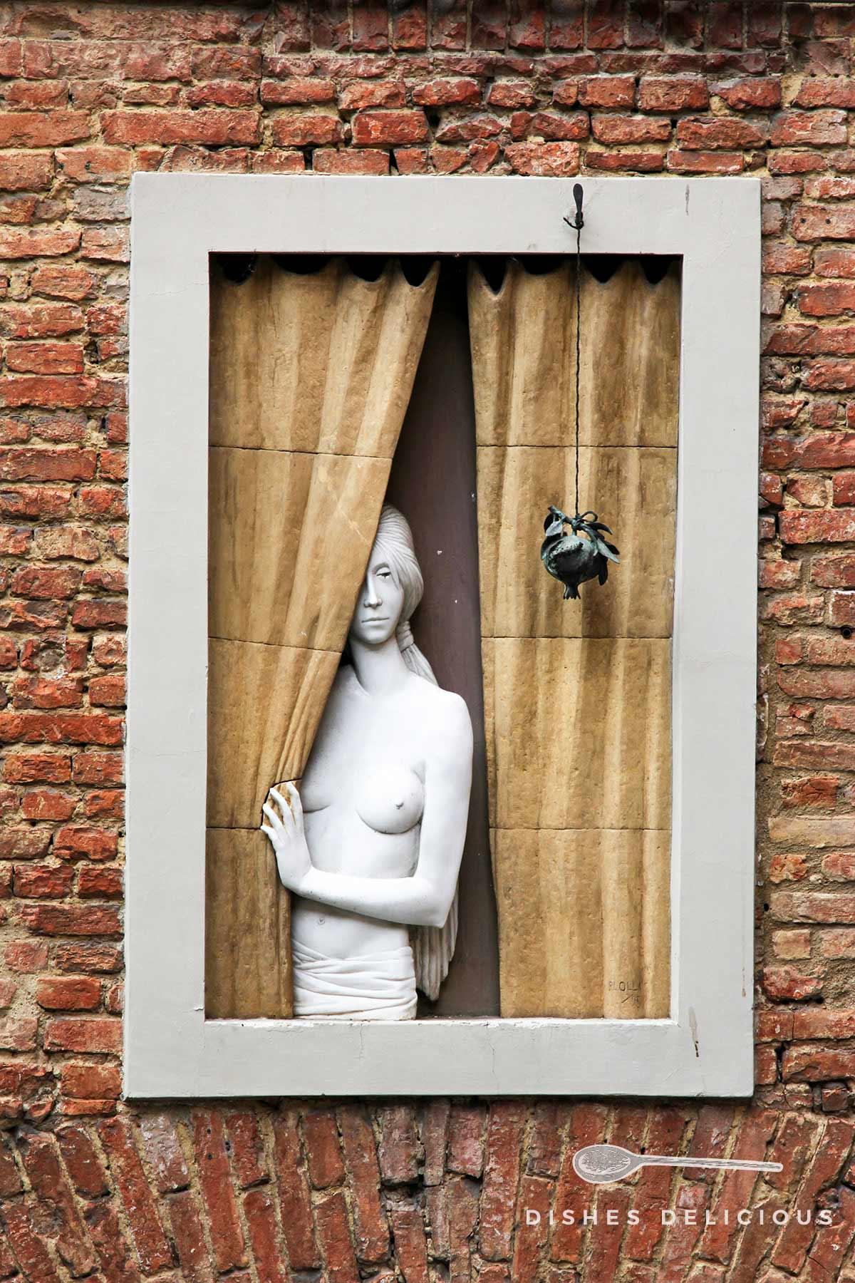 Wandskulptur mit einer Frau, die aus dem Fenster blickt.