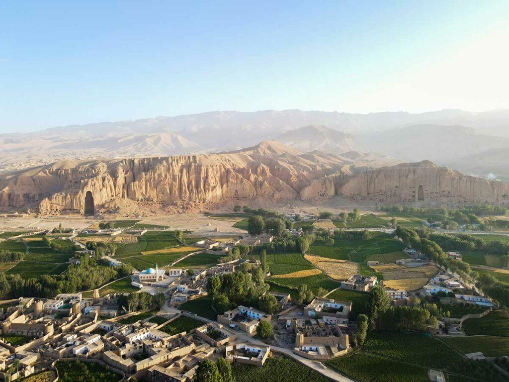 Foto von Bamiyan in Afghanistan, Im Vordergrund grüne Wiesen und Gebäude, im Hintergrund die kargen Berge.