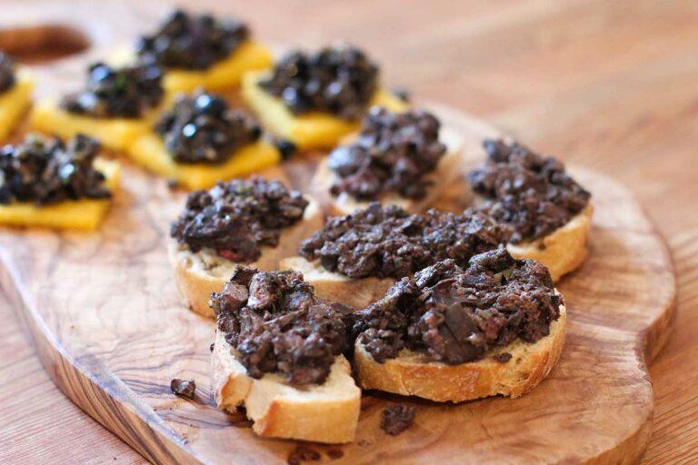 Foto von einem Holzbrett, auf dem mehrere mit einer Oliven-Fleischmasse belegte Crostini toscani liegen.