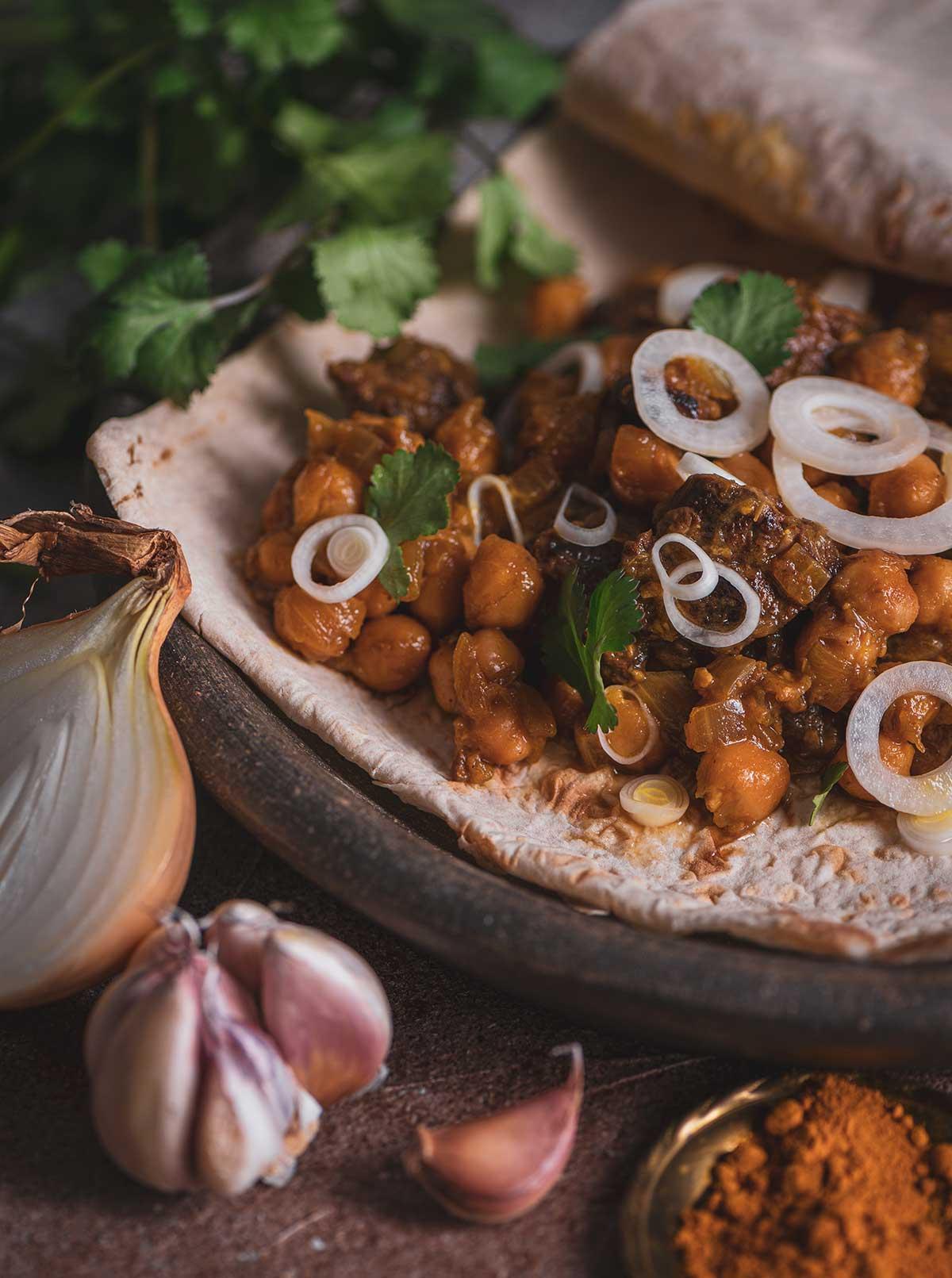 Foto von Zwiebelfleisch mit Kichererbsen auf Fladenbrot.