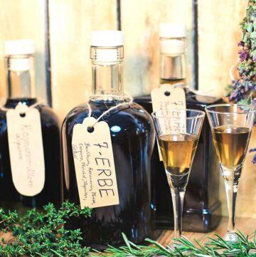 Foto von mehreren Flaschen mit Kräuterlikör und zwei Gläsern mit Likör.