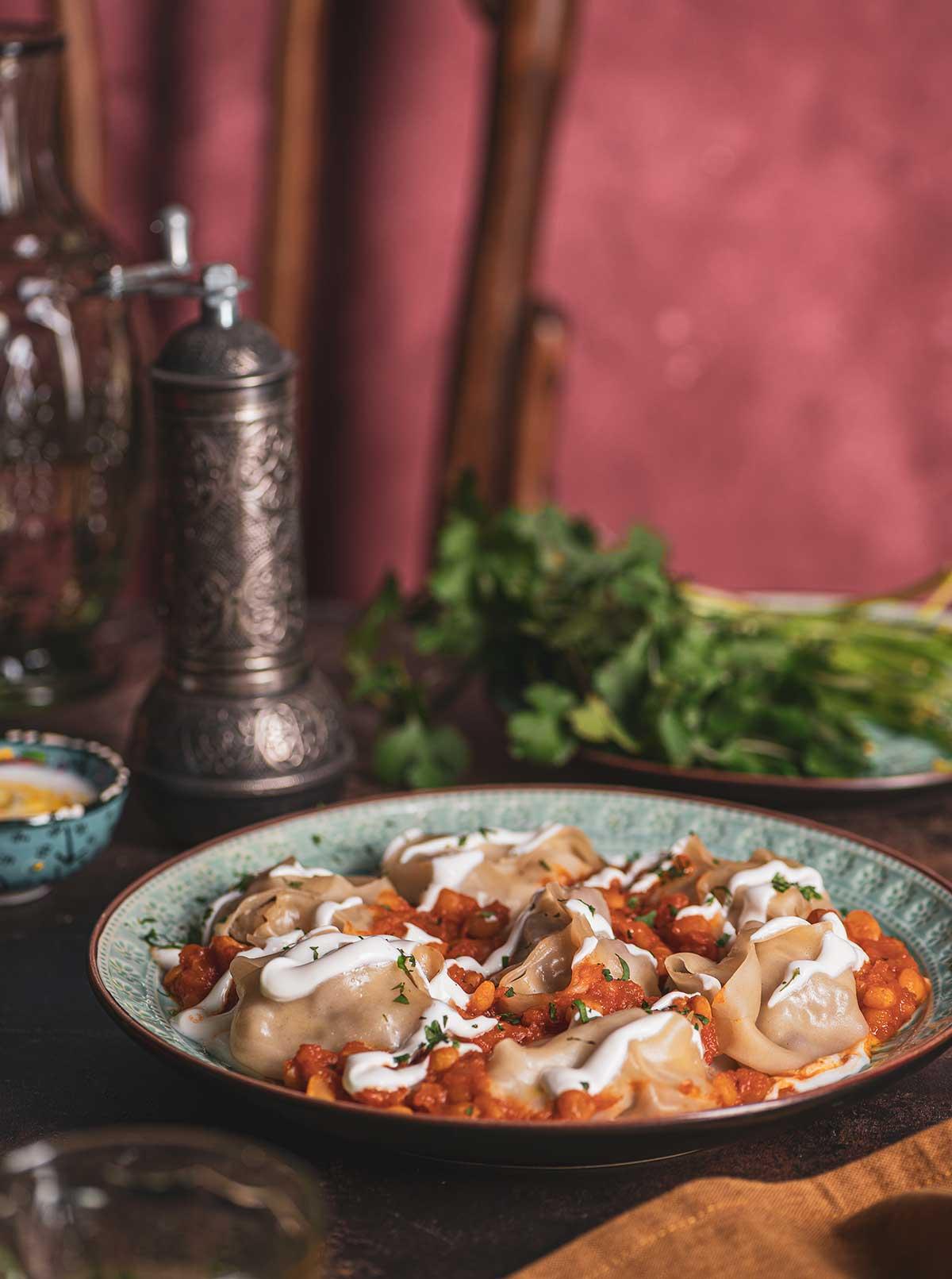 Foto von mit Joghurt garnierten Mantu-Teigtaschen auf einem Teller.
