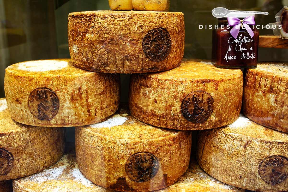 Foto von mehreren aufeinandergestapelten Käselaiben Pecorino Toscano.