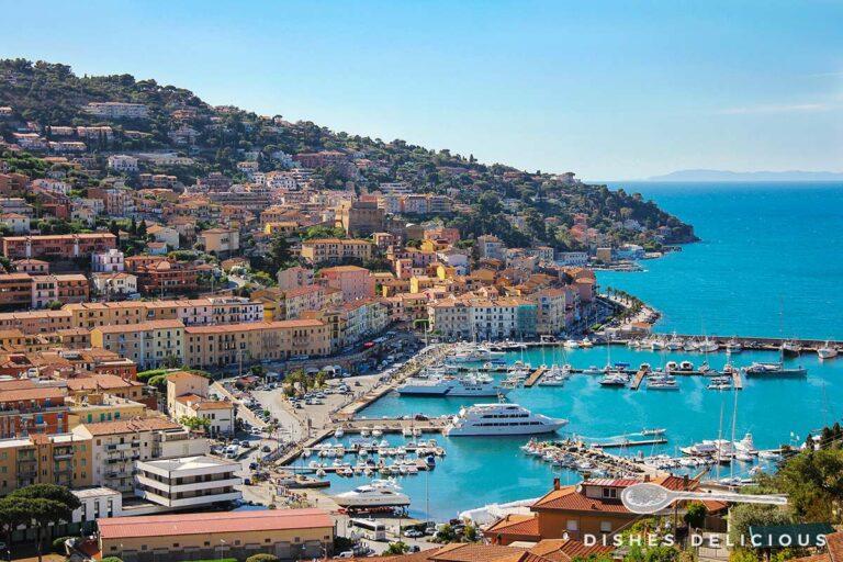 Panoramafoto von Porto Santo Stefano, das sich am Hang entlangzieht, im Vordergrund der Hafen.