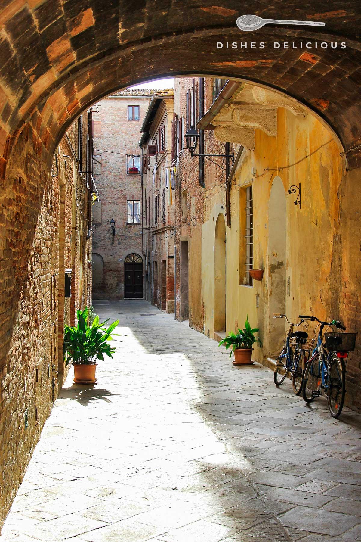 Foto einer Gasse in Buonkonvento, über die sich ein mittelalterlicher Bogen spannt. An der Seite sind zwei Fahrräder abgestellt.
