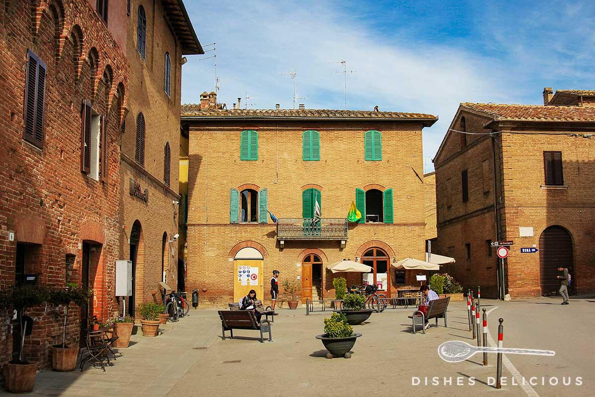 Foto der Piazza Matteotti in Buonconvento: vor den Backstein-Palazzi stehen mehrere Sitzbänke.