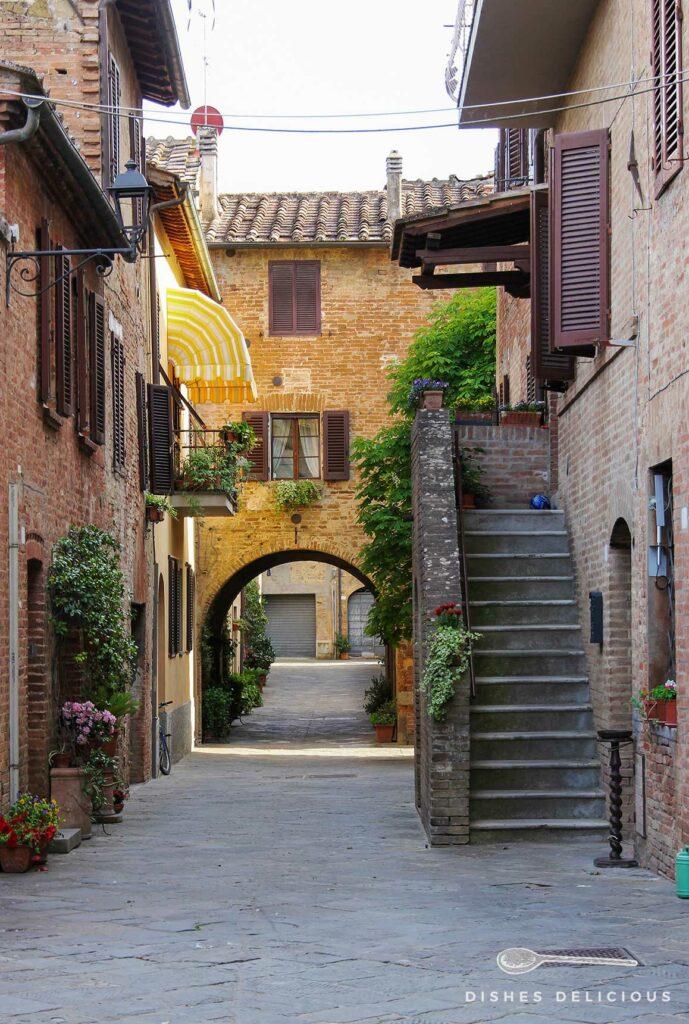 Foto einer Gasse in Buonconvento. Eine Treppe führt zu einem Hauseingang, im Hintergrund verbindet ein Bogen zwei Häuser.