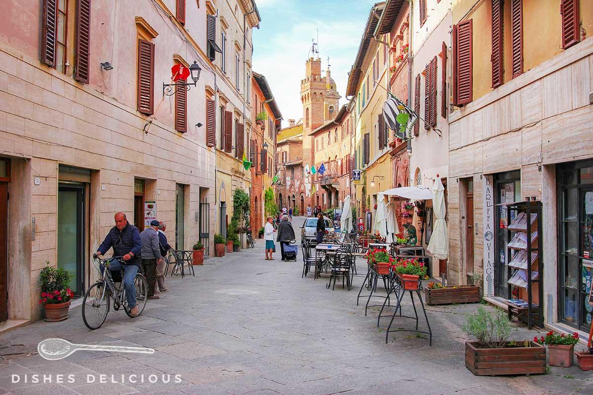 Foto der Via Soccini in Buonconvento: Trattorien laden zum Verweilen ein, ein Mann fährt Fahrrad.