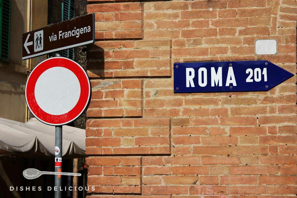 Foto von mehreren Straßenschildern an einem Backsteinbau. Ein Schild weist in Richtung Rom
