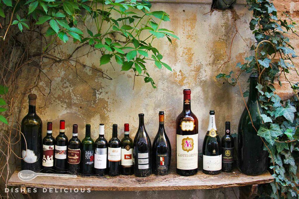 Foto von mehreren leeren Weinflaschen, die auf einem Holzbrett aufgereiht sind.