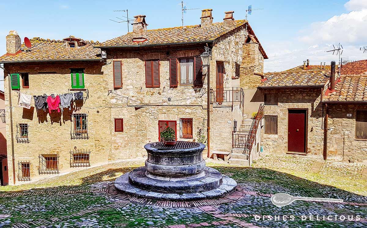 Foto eines mittelalterlich wirkenden Platzes in Castiglione - im Zentrum steht ein alter Brunnen.