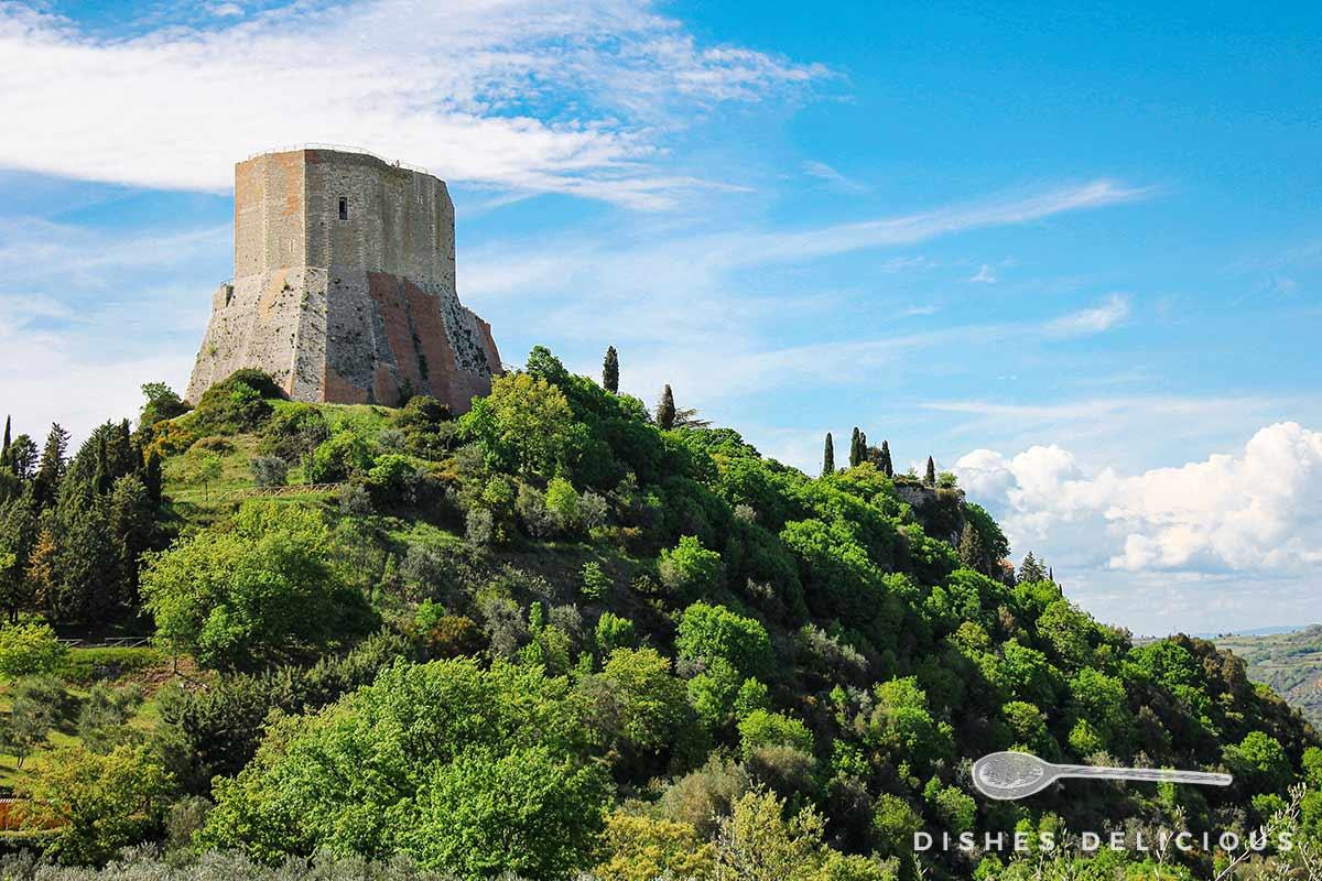 Foto vom Festungsturm Rocca di Tentennano auf einem bewaldeten Hügel.