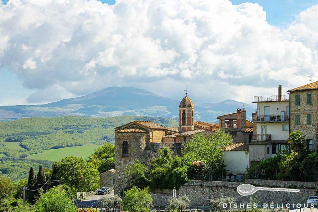 Foto von der Kirche Santi Stefano e Degna in Castiglione d'Orcia, im Hintergrund die Landschaft der Toskana.