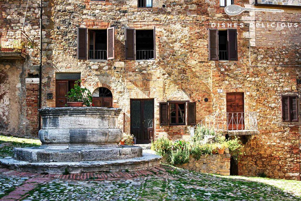 Foto von einem alten Backsteinhaus mit Brunnen in Castiglione d'Orcia.