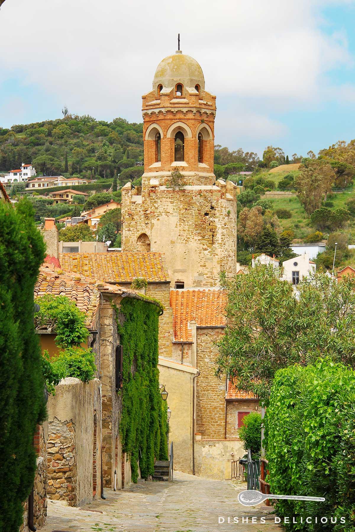Foto der Kirche Giovanni Battista in Castiglione della Pescaia, zu der ein gepflasterter Weg führt.