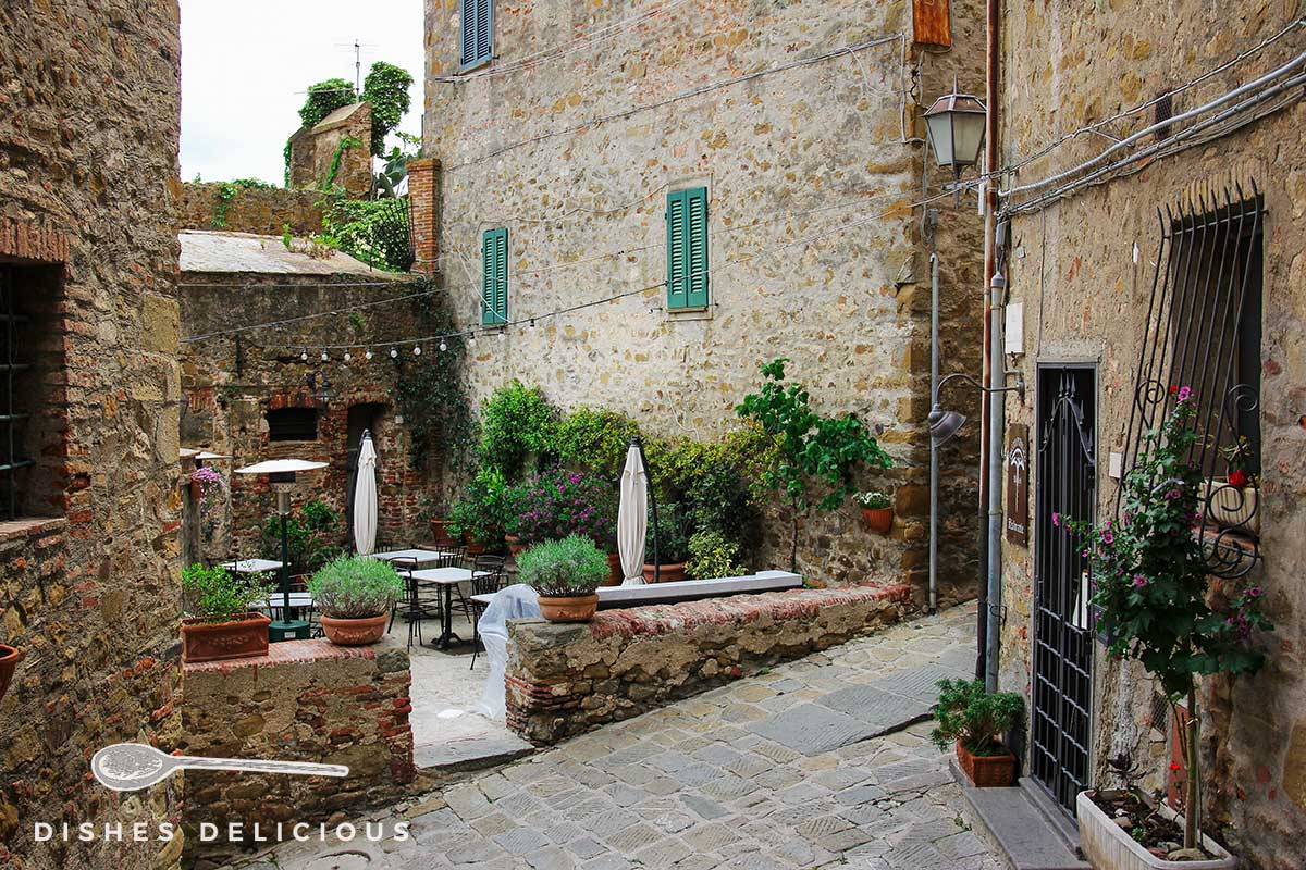 Foto von einem Innenhof in der Altstadt von Castiglione della Pescaia, in dem verlassene Tische einer Trattoria auf Gäste warten.