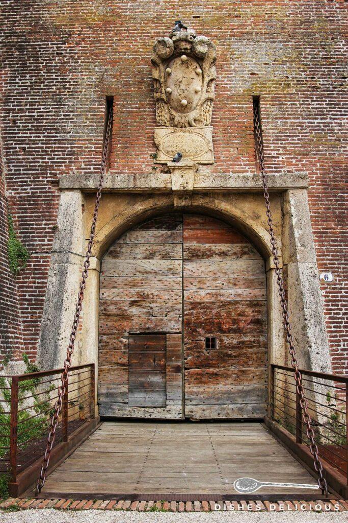 Foto vom Eingangsportal des Cassero Senese, über dem ein steinernes Medici-Wappen angebracht ist.