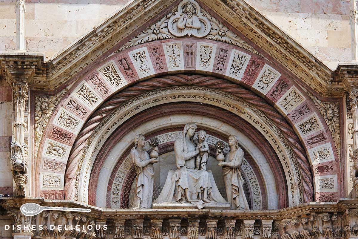 Foto einer Steinverzierung am Dom von Grosseto, die Maria mit Jesus zwischen zwei Heiligen zeigt.