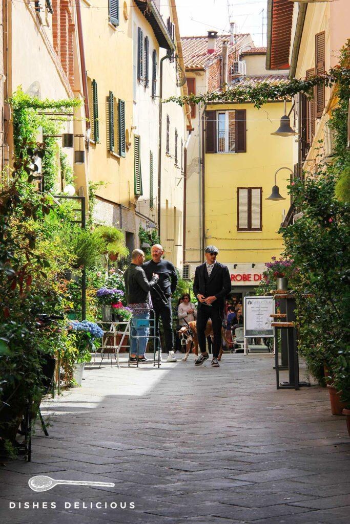 Foto einer Gasse in Grosseto. Drei Männer unterhalten sich.