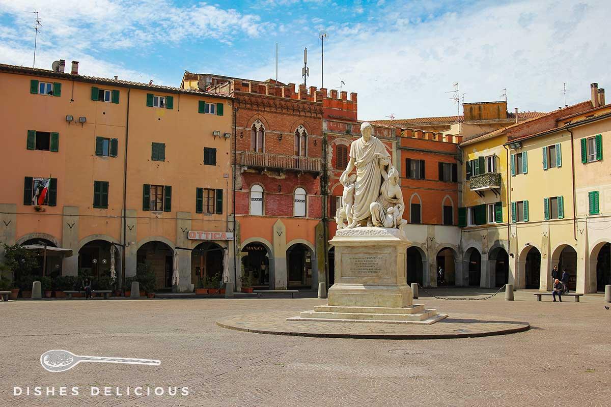 Foto der Piazza Dante - in der Mitte steht eine Statue, dahinter viele alte Gebäude.