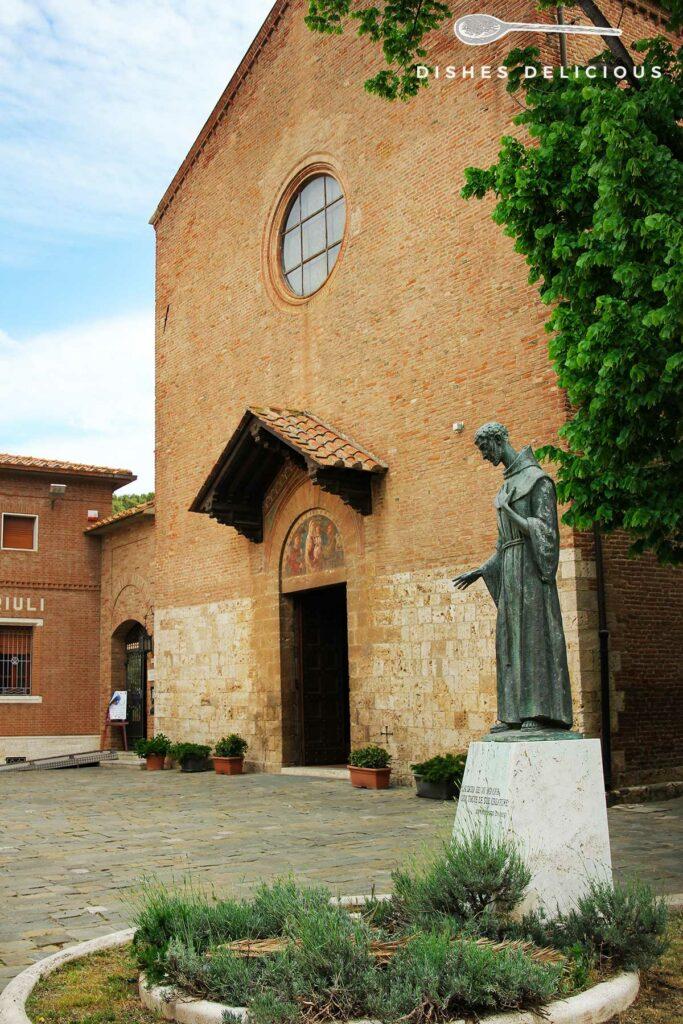 Foto der Kirche San Francesco mit einer Statue des Heiligen Franziskus im Vordergrund.