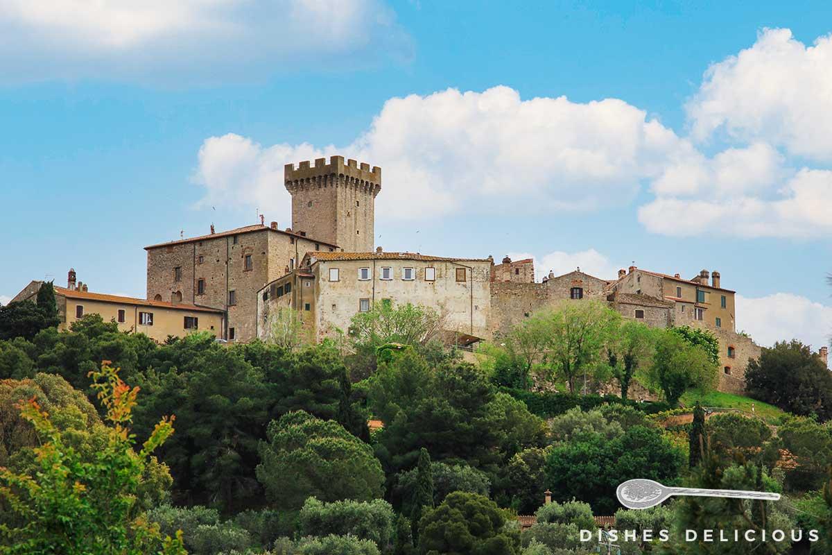 Foto des mittelalterlichen Orts Capalbio, aus dem ein Turm hervorsticht.
