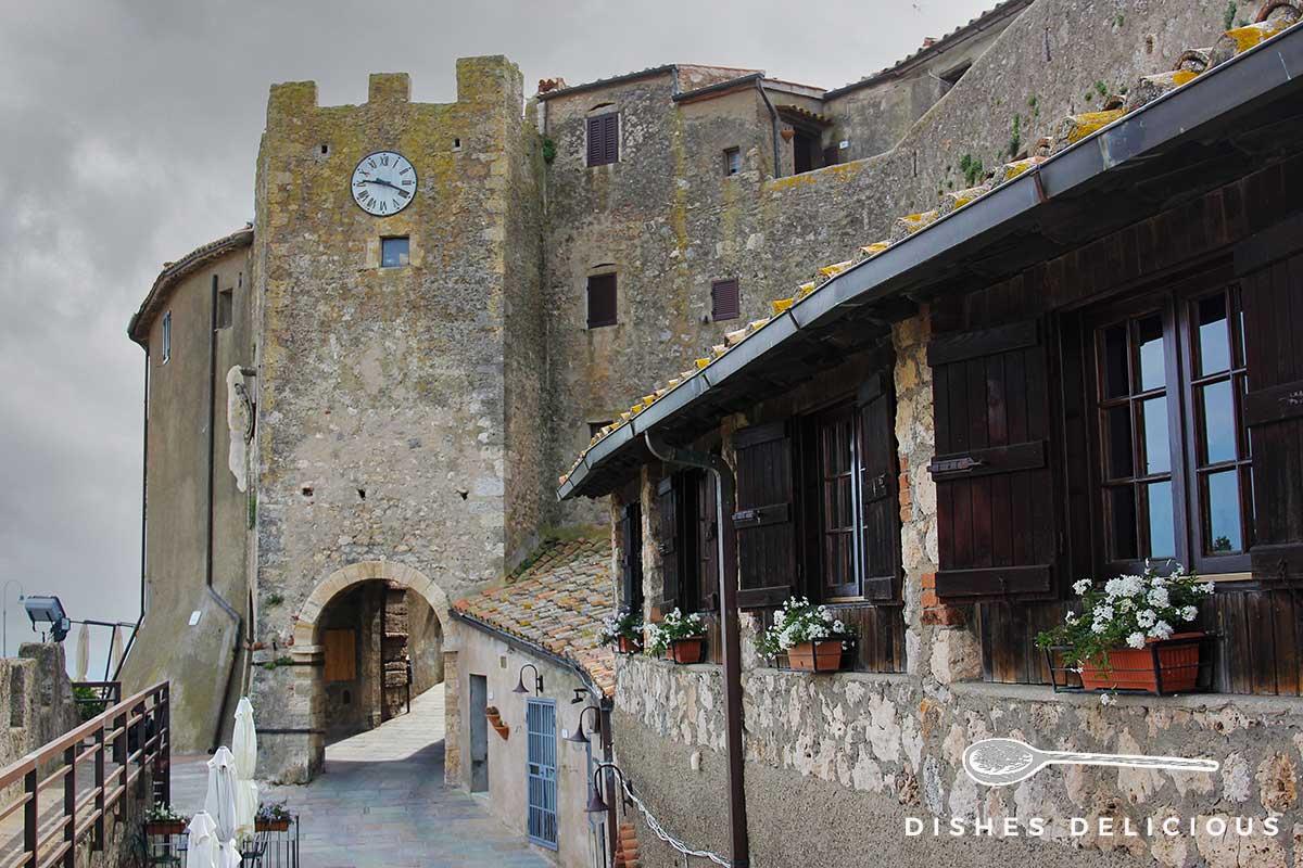 Foto eines wuchtigen Turms in Capalbio, durch einen Bogen geht man in die Altstadt.