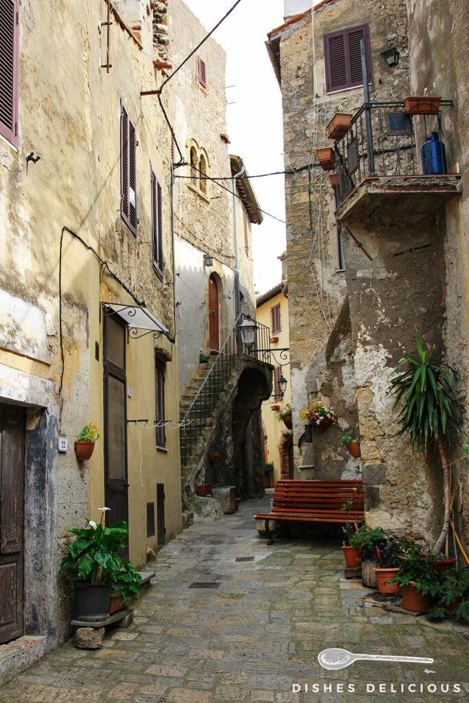 Foto einer engen Gasse in Capalbio, vor einem Haus steht eine Sitzbank.