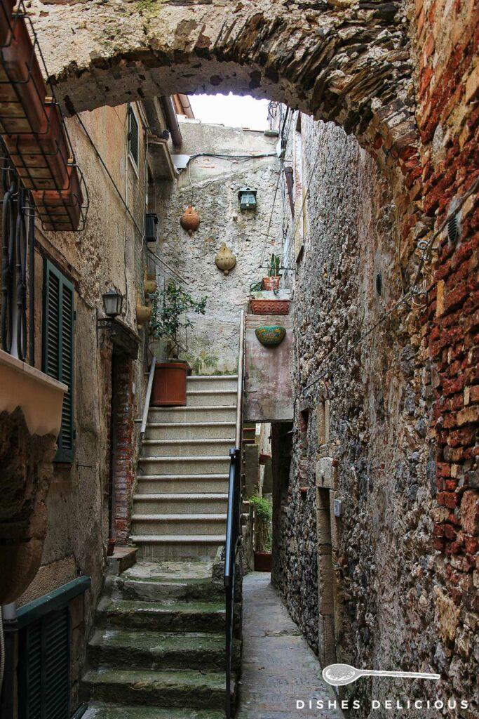 Foto einer sehr engen Gasse, die durch eine Treppe zu einem Hauseingang zusätzlich verschmalert wird.