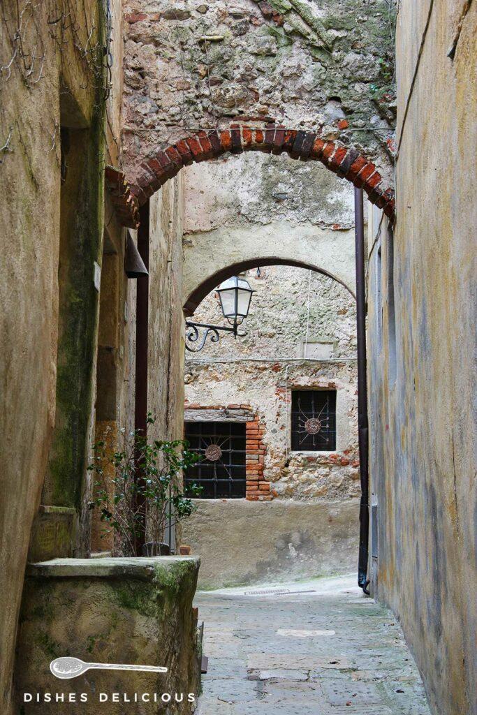 Foto einer schmalen Gasse in Capalbio, über die sich mehrere Steinbögen spannen.