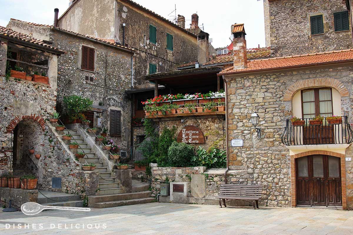 Foto der Piazza Magenta. Grob gemauerte Steinhäuser und viele Pflanzen sorgen für eine gemütliche Atmosphäre.