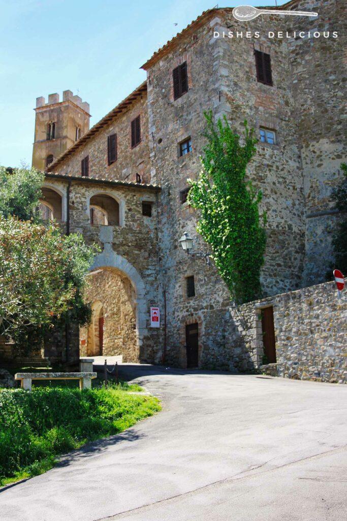 Foto des alten Stadttors San Giorgio in Montemerano, im Hintergrund ragt ein Turm in die Höhe.