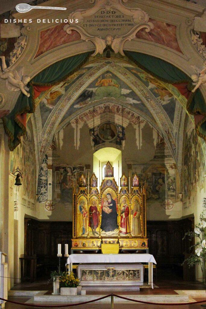 Foto vom Innenraum der Chiesa San Giorgio - im Mittelpunkt steht der Altar, über den sich die verzierte Decke spannt.